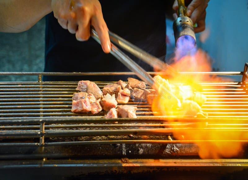 Mężczyzny opieczenia plasterek mięso na kuchence z płomieniem od benzynowej drymby obraz stock
