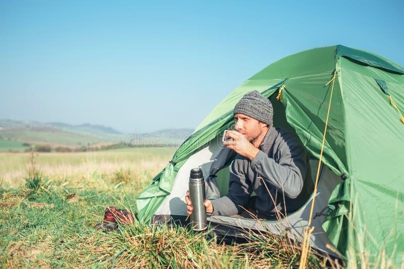 Mężczyzny podróżnik spotyka nowego dzień w namiocie, pije gorącego herbacianego siedzącego insid zdjęcie royalty free