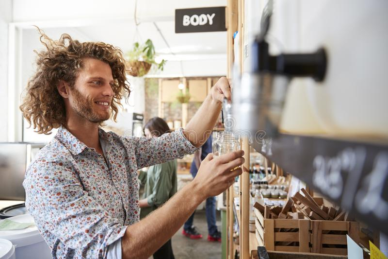 Mężczyzny Podsadzkowy zbiornik Z zmywarkiego do naczyń proszkiem W klingerycie Uwalnia sklep spożywczego obrazy royalty free