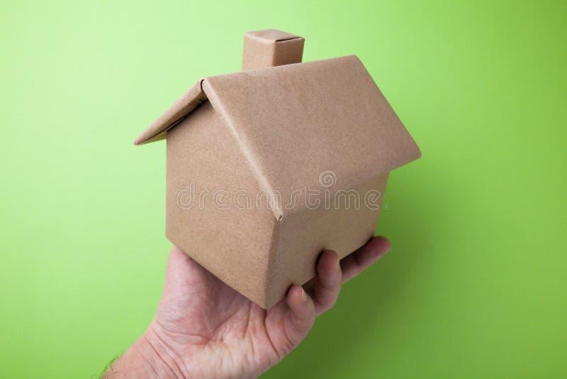 Mężczyzny ręka trzyma a w górę kartonowego domu Zielony t?o zdjęcia royalty free