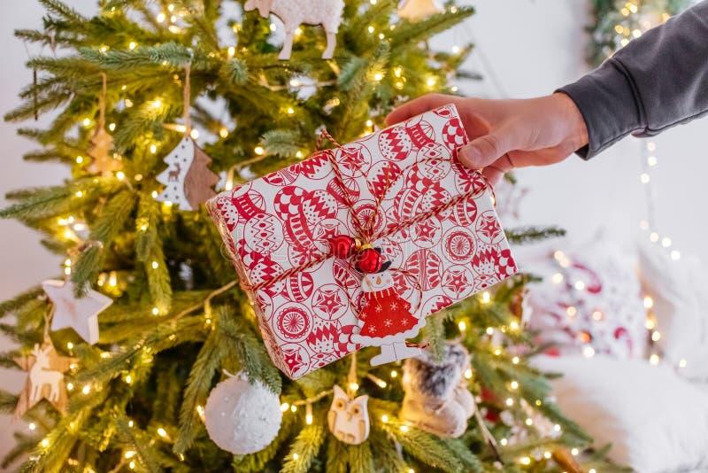 Mężczyzny ręka trzyma za prezencie pod drzewem wygodny Bożenarodzeniowy wystrój girlandy bokeh Nowy rok 2019 obrazy stock