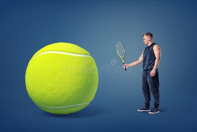 Mężczyzny sportowi stojaki w bocznym widoku trzyma tenisowego racquet przed gigantyczną żółtą piłką obraz stock