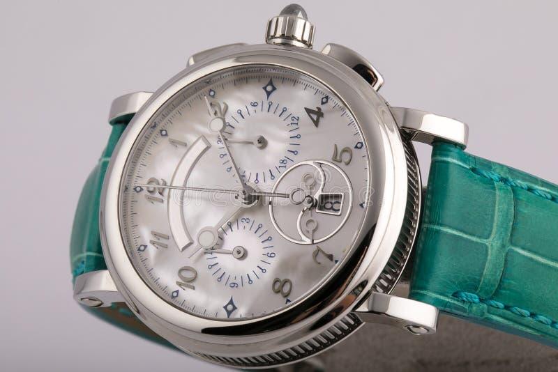 Mężczyzny srebny zegarek z białą tarczą, osrebrza clockwise chronograf z zieloną rzemienną patką odizolowywającą na białym tle obrazy royalty free
