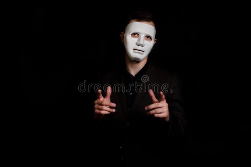 Mężczyzny stojaki na czarnym tle w białej masce Robi gestowi trzyma za jego rękach i wskazuje z jego palcem, obrazy stock