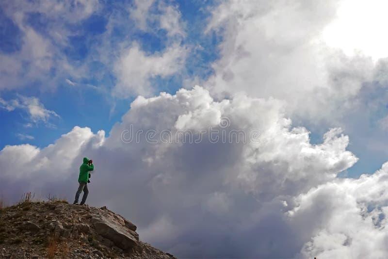 Mężczyzny stojaki na górze i robią fotografii chmury zdjęcia royalty free