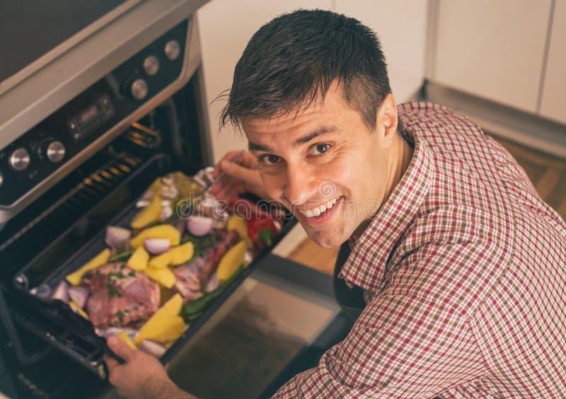 Mężczyzny wypiekowy mięso w piekarniku zdjęcie royalty free