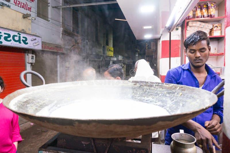 Mężczyzny zsiadania mleko w ogromnej niecce robić indyjskim cukierkom zdjęcie stock