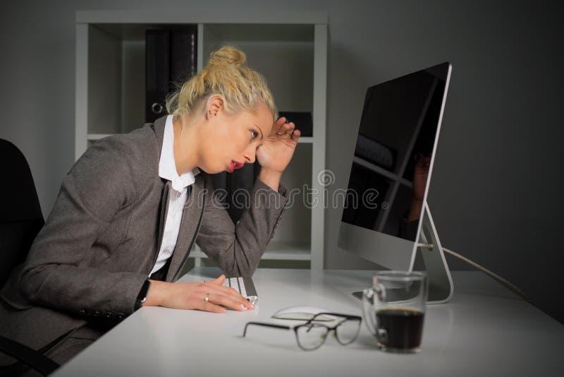 Męcząca i dokuczająca kobieta pracuje na komputerze przy biurem zdjęcia stock