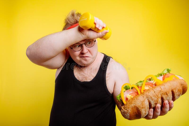 Męczący grubi mężczyzna poty podczas gdy podnoszący hamburger obrazy royalty free