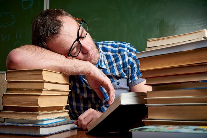 Męczący i torturujący rozkudłany uczeń w szkłach śpi przy stołem na stercie książki fotografia royalty free