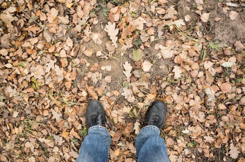 Męscy cieki w niebieskich dżinsach i czerń butach na brudnej ziemi obraz royalty free