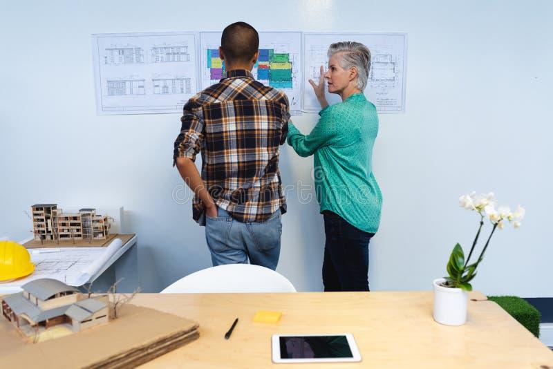 Męscy i żeńscy architekci dyskutuje nad architektonicznym planem w biurze zdjęcia stock