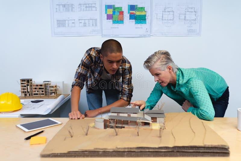Męscy i żeńscy architekci dyskutuje nad wzorcową strukturą dom przy biurkiem zdjęcia royalty free