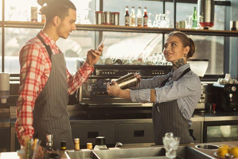 Męscy i żeńscy barmany przy sklep z kawą kontuarem zdjęcia stock