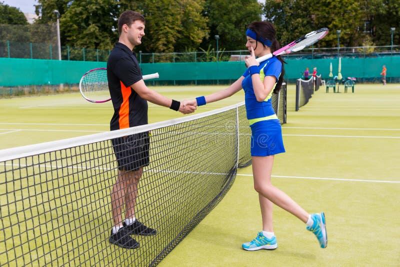 Męscy i żeńscy gracz w tenisa trząść ręki nad siecią zdjęcia stock