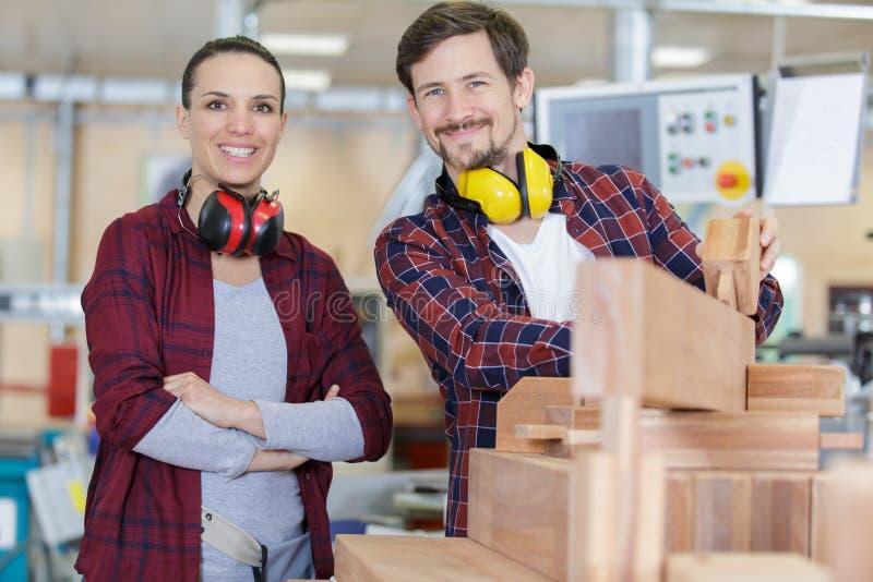 Męscy i żeńscy pracownicy w woodworking warsztacie obrazy stock
