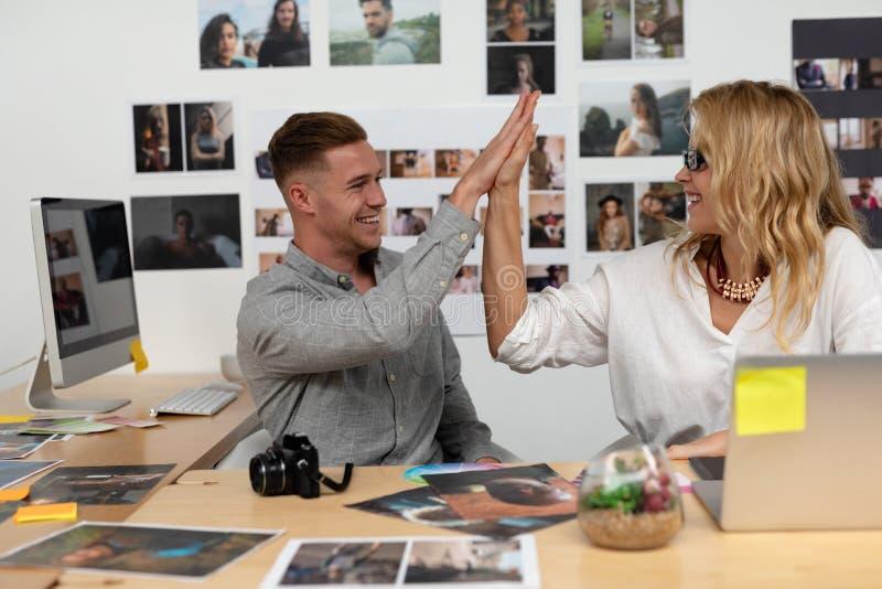 Męscy i żeńscy projektant grafik komputerowych daje wysokości pięć do siebie przy biurkiem obraz stock
