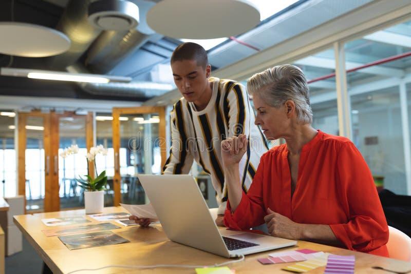 Męscy i żeńscy projektant grafik komputerowych dyskutuje nad fotografiami przy biurkiem fotografia stock