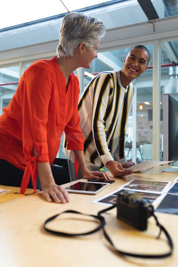 Męscy i żeńscy projektant grafik komputerowych dyskutuje nad fotografiami przy biurkiem zdjęcie stock