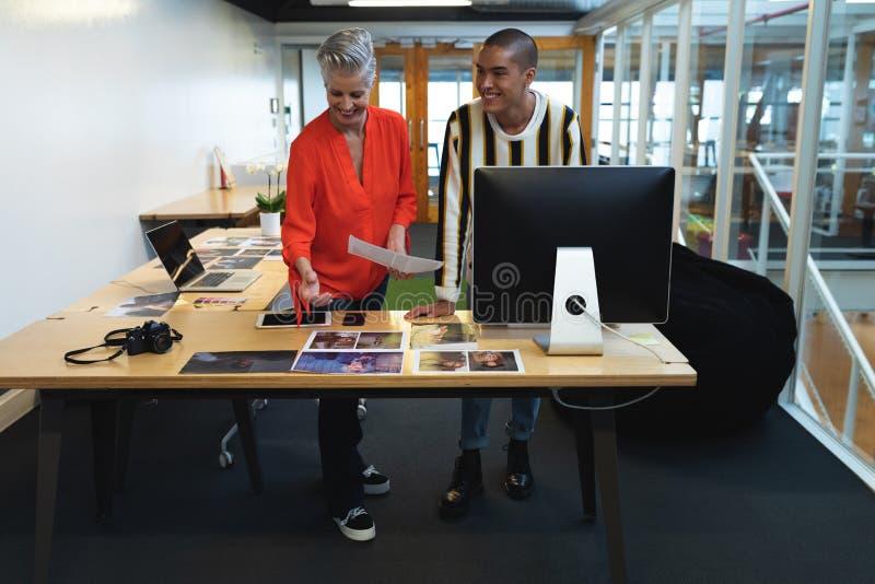 Męscy i żeńscy projektant grafik komputerowych dyskutuje nad fotografiami przy biurkiem obrazy stock