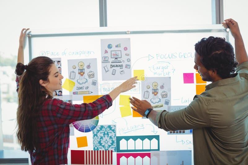 Męscy i żeńscy projektant grafik komputerowych dyskutuje nad kleistymi notatkami zdjęcia royalty free
