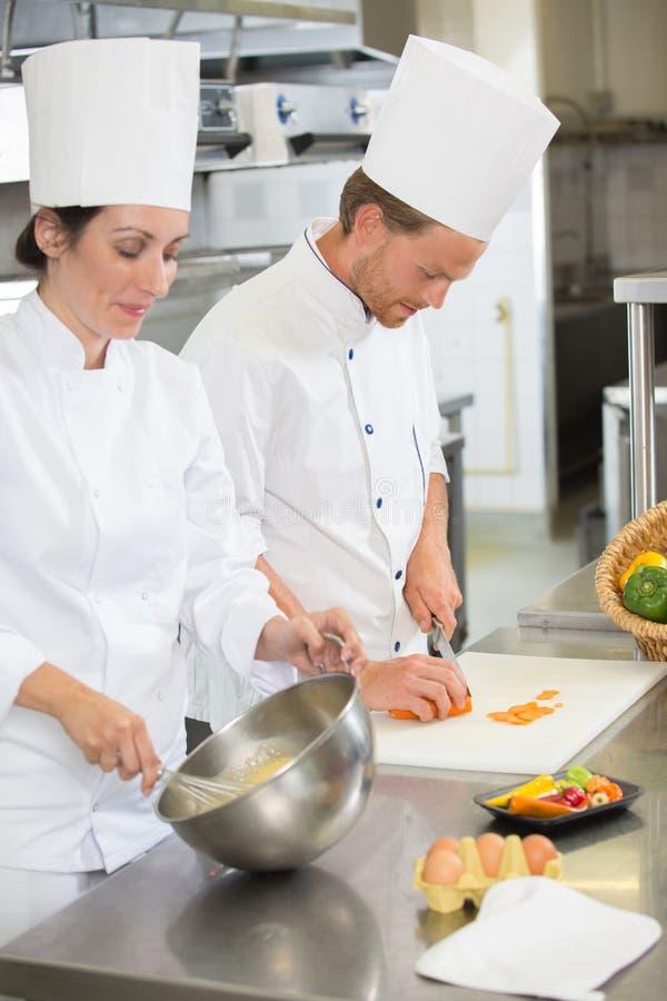 Męscy i żeńscy szefowie kuchni pracuje przy restauracyjną kuchnią zdjęcia stock