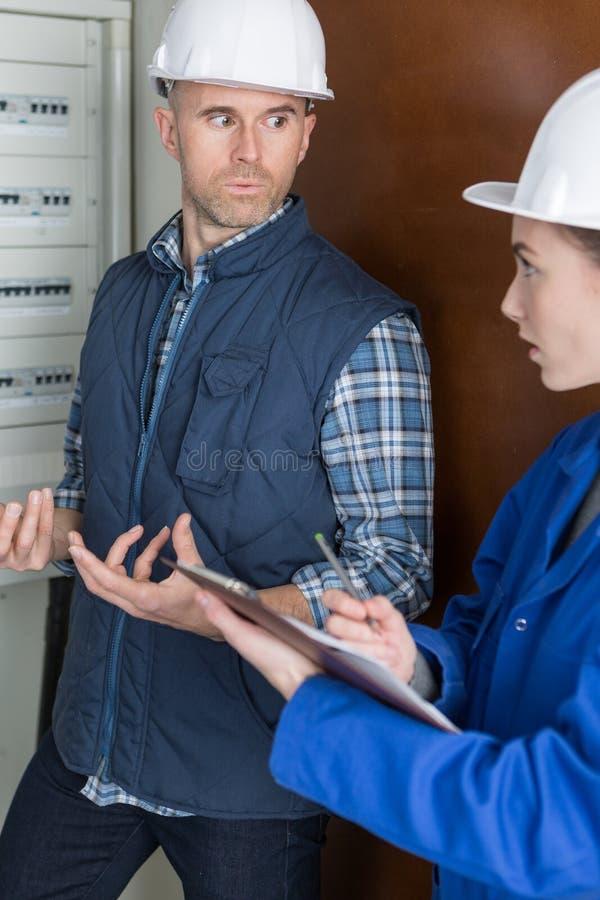 Męscy i żeńscy technicy w dyskusi elektrycznym fusebox obrazy stock