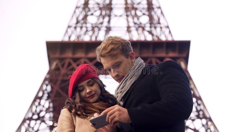 Męscy i żeńscy turyści szuka miejsce przeznaczenia w Paryż na mapie w wiszącej ozdobie app zdjęcie royalty free