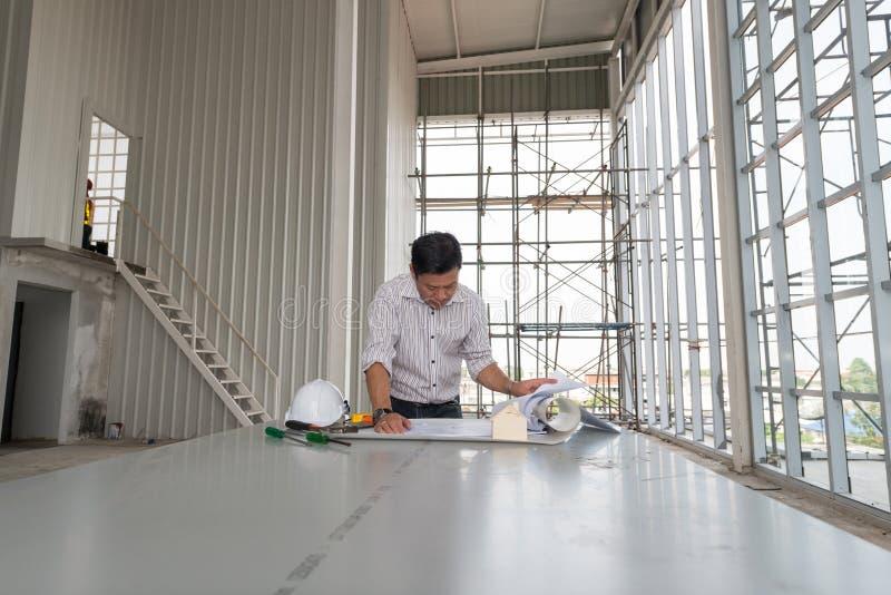 Męscy inżyniery stoją zegarka modela w budynek budowie zdjęcia stock