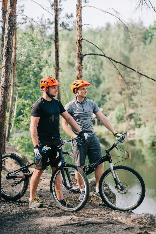 męscy próbni rowerzyści odpoczywa z sport butelkami wodna pobliska rzeka w hełmach z halnymi cyklami zdjęcia stock