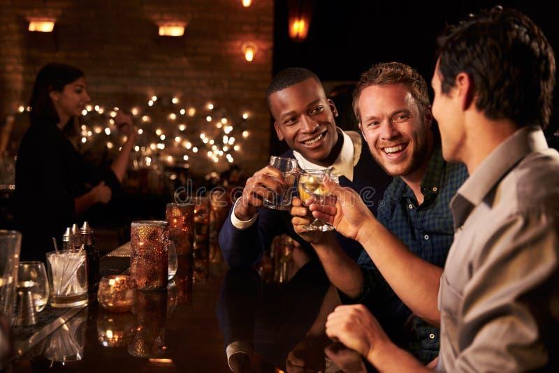 Męscy przyjaciele Cieszy się noc Out Przy koktajlu barem zdjęcia royalty free
