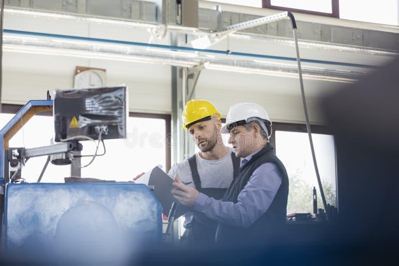 Męscy ręczni pracownicy działa maszynerię przy metalu przemysłem obraz stock