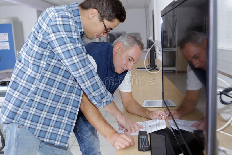 Męscy technicy sprawdza telewizję obrazy stock
