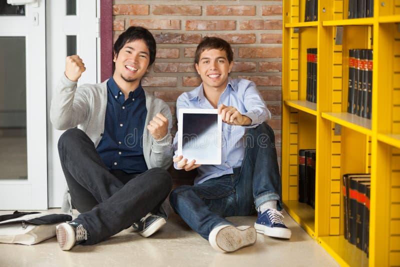 Męscy ucznie Pokazuje Cyfrowej pastylkę Podczas gdy Siedzący zdjęcia stock
