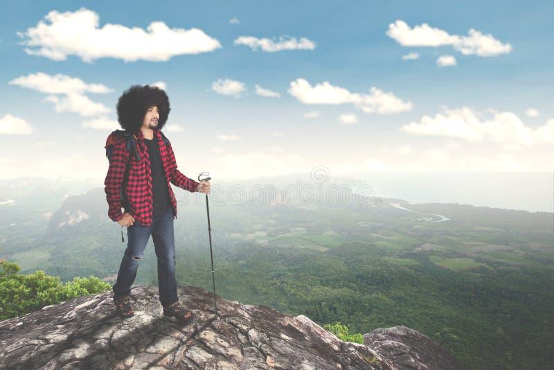 Męska Afro wycieczkowicza pięcia skała na wzgórzu obraz royalty free