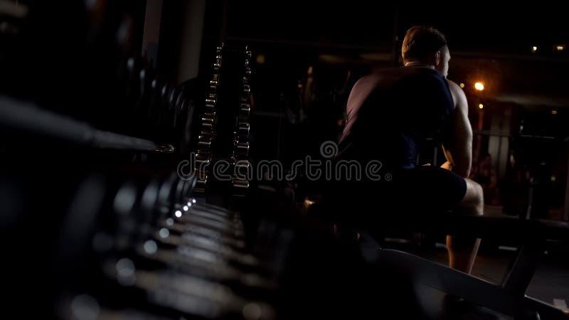 Męska atleta męcząca, garbi się w górę wieczór gym samotnie wewnątrz po tym jak trening siedzi na ławce obrazy stock
