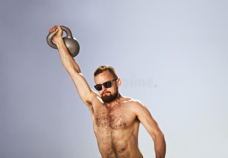 Męska atleta wykonuje jednoręczne czajnika dzwonu huśtawki obraz royalty free