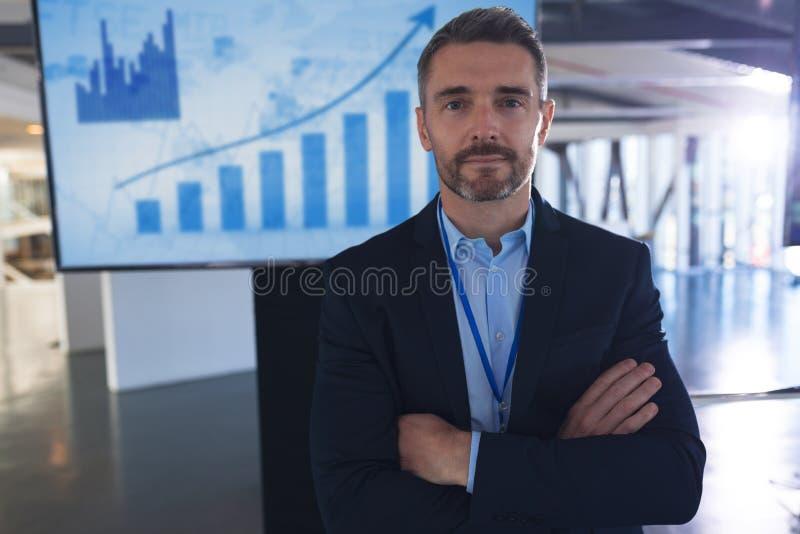 Męska głośnikowa pozycja z rękami krzyżował w biznesowym konwersatorium zdjęcia stock