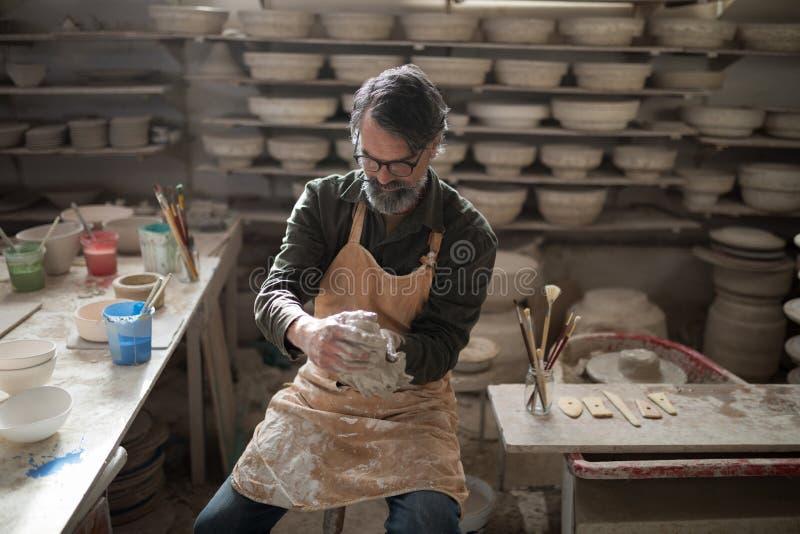 Męska garncarka pleśnieje glinę zdjęcie royalty free