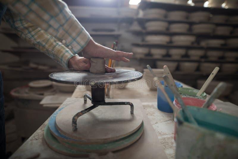 Męska garncarka pleśnieje glinę na ceramicznym kole obraz royalty free