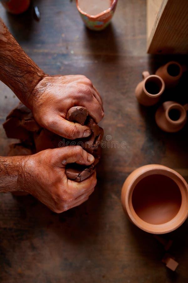 Męska garncarka pleśnieje glinę w ceramicznym warsztacie, zakończenie, selekcyjna ostrość, odgórny widok zdjęcie royalty free