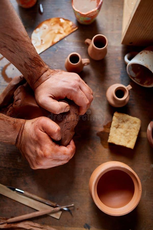 Męska garncarka pleśnieje glinę w ceramicznym warsztacie, zakończenie, selekcyjna ostrość, odgórny widok fotografia stock