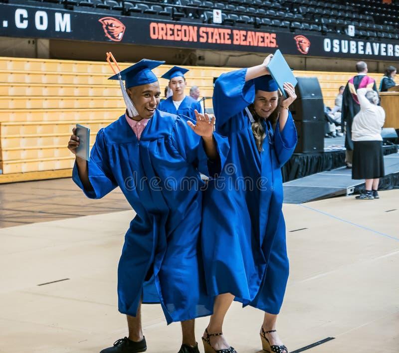 Męska i żeńska szkoła średnia kończy studia seniorów wpadać na siebie biodra świętować dyplomy obrazy royalty free