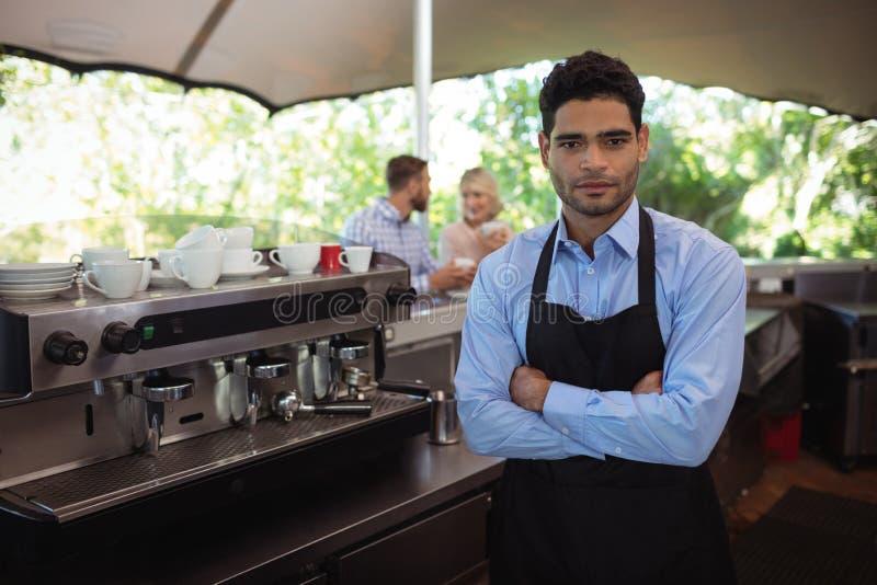 Męska kelner pozycja z rękami krzyżował w restauraci obraz royalty free