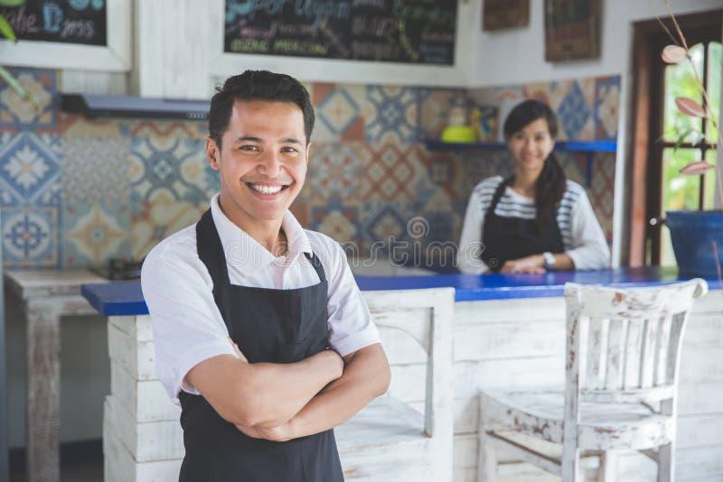 Męska kelnerki pozycja z rękami krzyżował w kawiarni obraz stock