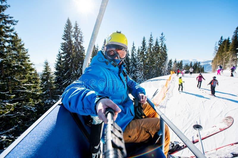 Męska narciarka używa selfie kij bierze fotografie podczas gdy narciarstwo zdjęcia stock