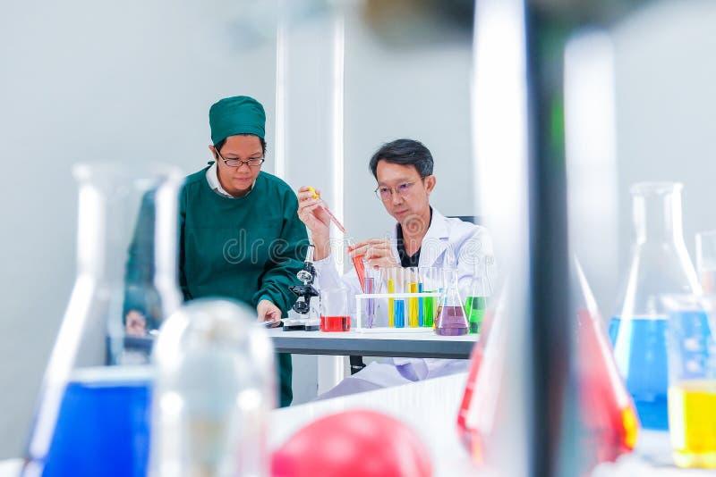 Męska naukowiec pozycja z techer w lab pracowniku robi medycznym obraz royalty free