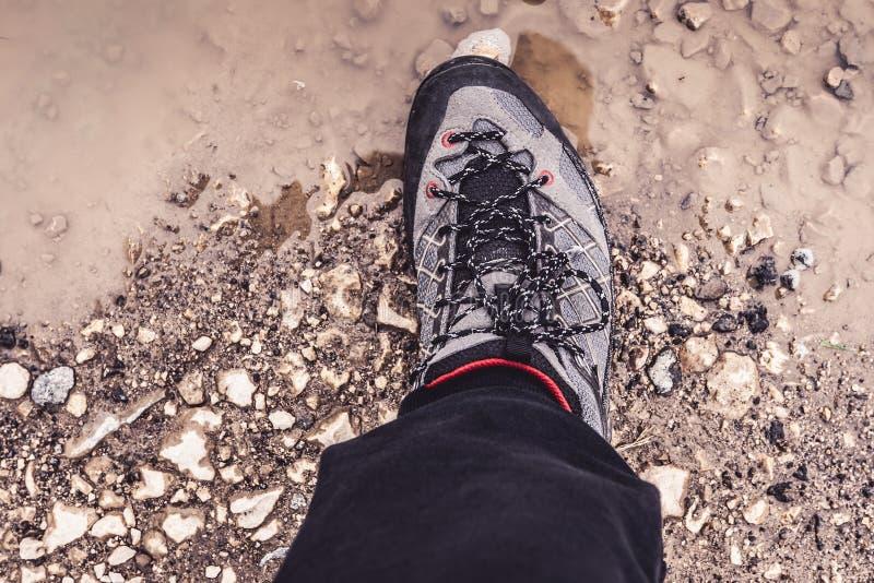 Męska noga Jest ubranym Sportive Wycieczkuje Sneakers buty w błocie i wodzie Trekking obuwie dla Halnego odprowadzenie śladu obraz royalty free