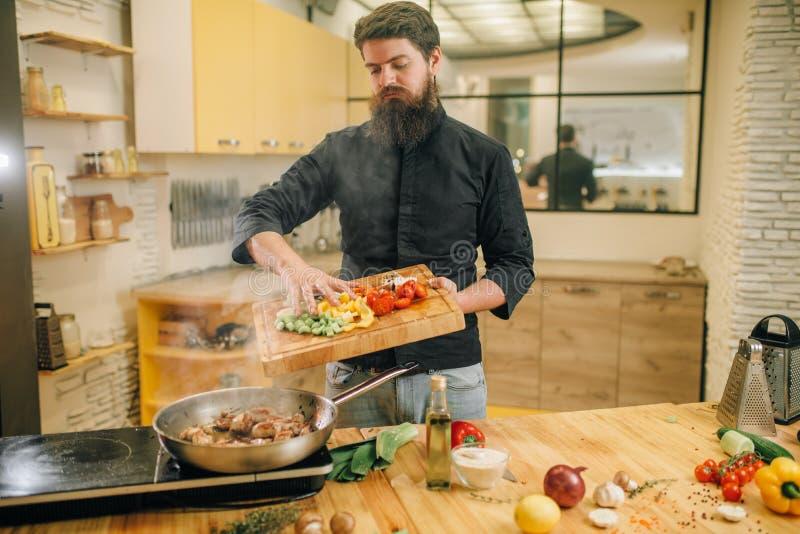 Męska osoba stawia warzywa w nieckę z mięsem zdjęcia stock