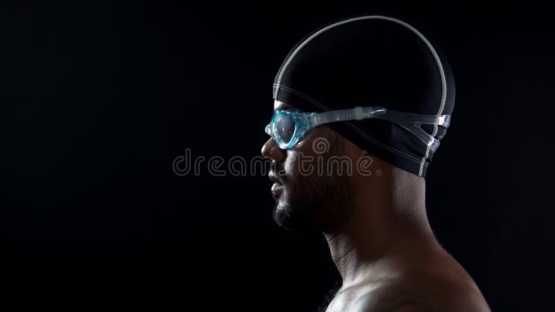 Męska pływaczka jest ubranym gogle i przygotowywa skakać w pływackiego basen, zakończenie zdjęcie royalty free